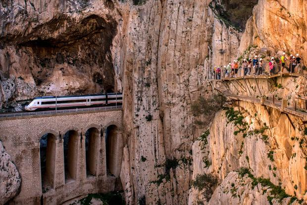 A train passes through a tunnel as tourists walk along the 'El Caminito del Rey' (King's Little Path) footpath on April 1, 2015 in Malaga, Spain.