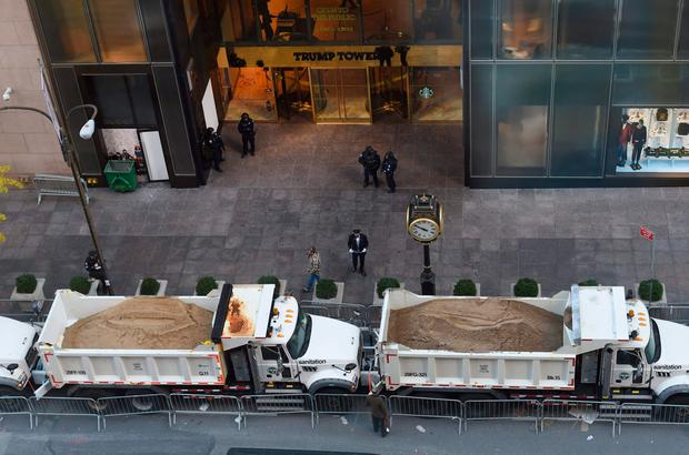 A protective barrier of Sanitation Department trucks are parked in front of Trump Tower on 5th Avenue to provide security to US President-elect Donald Trump on November 10, 2016 in New York. AFP/Getty Images