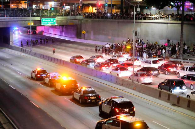 Police (L-under bridge) form a line across the road as demonstrators (R) shut down the 101 Freeway, a major thoroughfare in the city, following a rally to protest a day after President-elect Donald Trump's election victory in Los Angeles, California, late on November 9, 2016. Protesters burned a giant orange-haired head of Donald Trump in effigy, lit fires ins the streets and blocked traffic lanes late on November 9 as rage over the billionaire's election victory spilled onto the streets of US cities. From New York to Los Angeles, thousands of people in around 10 cities rallied against the president-elect a day after his stunning win, some carrying signs declaiming