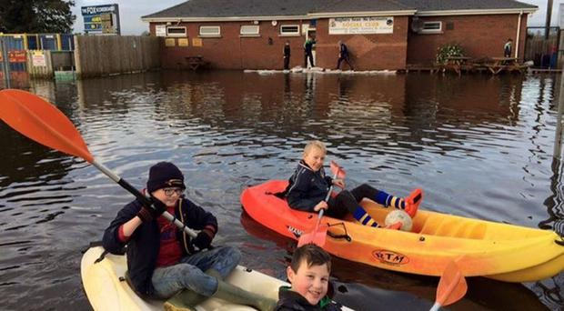 Water woe: Youngsters enjoy a paddle outside Maghery Sean McDermotts' social club after January's floods, but it was no joke for the club who were forced to launch a restoration project