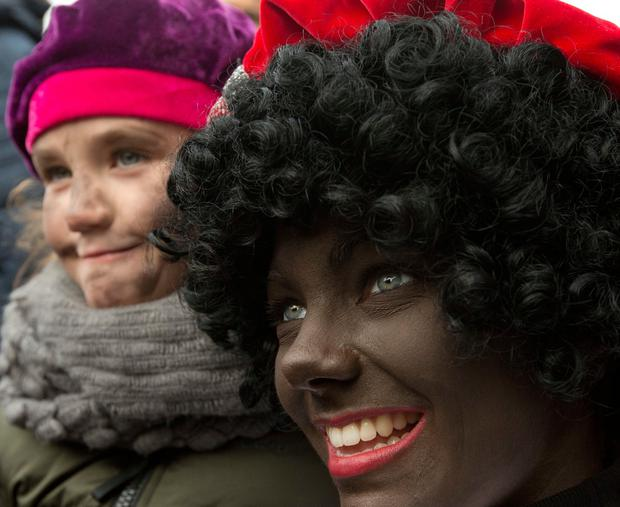 A Black Pete poses with a child during the arrival of Sinterklaas, or Saint Nicholas, in Maassluis, Netherlands, Saturday, Nov. 12, 2016. Sinterklaas and his helper Black Pete are at the center of a long-time controversy because Pete is often played by white people in blackface makeup. (AP Photo/Peter Dejong)