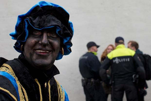 A Black Pete takes part in far-right demonstration in a closed off area while police officers question two people, rear, during the arrival of Sinterklaas, the Dutch Saint Nicholas, in Maassluis, Netherlands, Saturday, Nov. 12, 2016. Sinterklaas and his helper Black Pete are at the center of a long-time controversy because Pete is often played by white people in blackface makeup. (AP Photo/Peter Dejong)