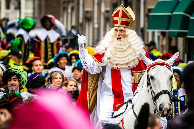 A man dressed as Sinterklaas (Saint Nicolas) gestures as he arrives on a horse in Maassluis on Novermber 12, 2016. Black Pete is the companion of Saint Nicolas during the Sinterklaas festival celebrated on the evening of 05 December, and has become the subject of much controversy in recent years as some people think it is racist. / AFP PHOTO / ANP / Remko de Waal / Netherlands OUTREMKO DE WAAL/AFP/Getty Images