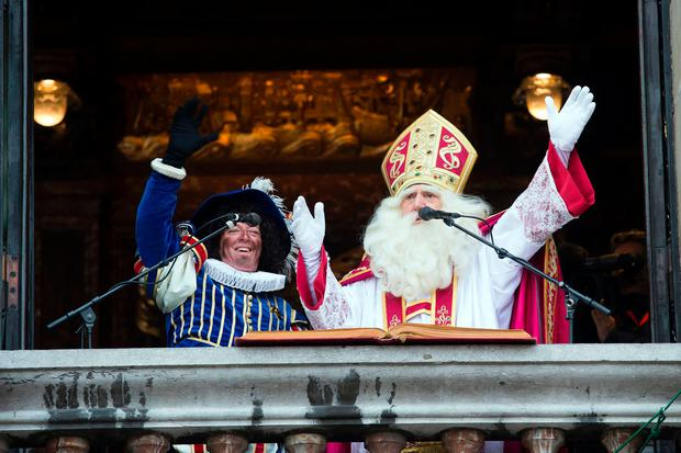 A man dressed as Sinterklaas (Saint Nicolas) and another one dressed as Zwarte Piet (Black Pete) gesture from a balcony on November 12, 2016 in Antwerp. Black Pete is the companion of Saint Nicolas during the Sinterklaas festival celebrated on the evening of 05 December, and has become the subject of much controversy in recent years as some people think it is racist. / AFP PHOTO / ANP / KRISTOF VAN ACCOM / Netherlands OUTKRISTOF VAN ACCOM/AFP/Getty Images