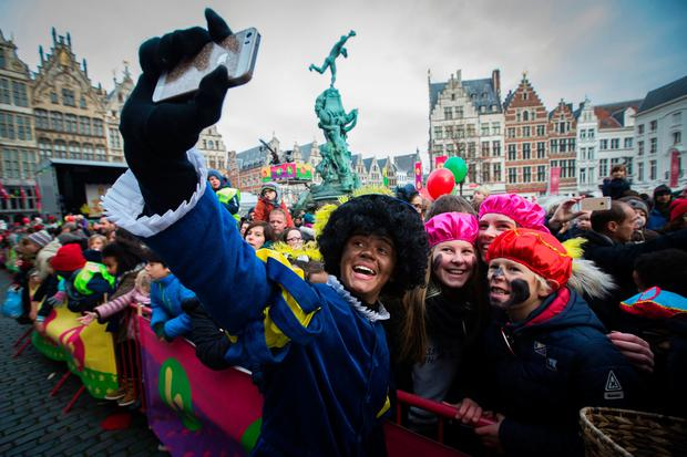 Children take a selfie with a man dressedas Zwarte Piet (Black Pete) during the traditionnal arrival of Sinterklaas (Saint Nicolas) on November 12, 2016 in Antwerp. Black Pete is the companion of Saint Nicolas during the Sinterklaas festival celebrated on the evening of 05 December, and has become the subject of much controversy in recent years as some people think it is racist. / AFP PHOTO / ANP / KRISTOF VAN ACCOM / Netherlands OUTKRISTOF VAN ACCOM/AFP/Getty Images