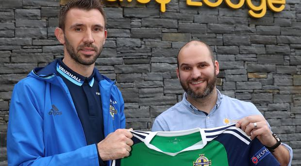 Gareth McAuley hands over his shirt he wore against Ukraine in the Euro's to Phil Alexander, Therapeutic Service Manager at Daisy Lodge for an online raffle. William Cherry/Presseye