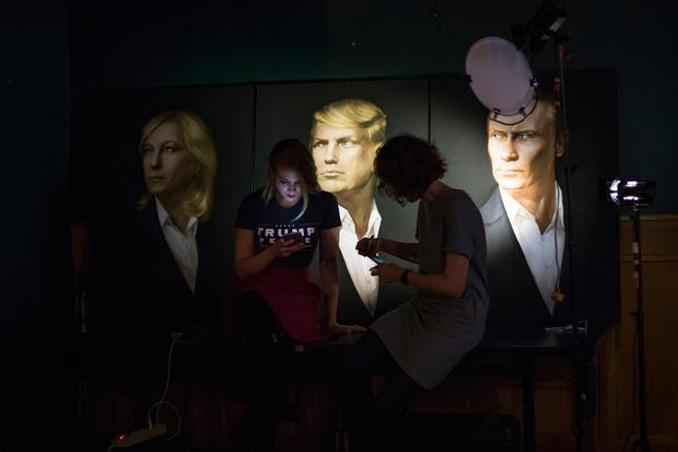 Two women look at their cell phones in front of portraits of U.S. President-elect Donald Trump and Russian President Vladimir Putin, right, as they arrive at the Union Jack pub in Moscow, Russia, to watch a live telecast of the U.S. presidential election on Wednesday, Nov. 9, 2016. (AP Photo/Alexander Zemlianichenko)