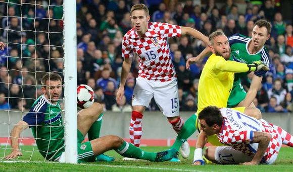 Croatia's midfielder Mario Mandzukic (R) scores his team's first goal past Northern Ireland's goalkeeper Alan Mannus during the friendly international football match between Northern Ireland and Croatia at Windsor Park in Belfast on November 15, 2016. AFP/Getty Images