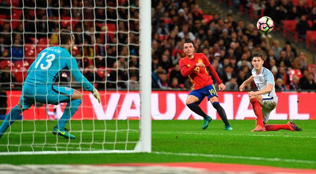 Not over yet: Iago Aspas begins the late fightback by curling Spain's first goal past Tom Heaton while England defender John Stones looks on helplessly
