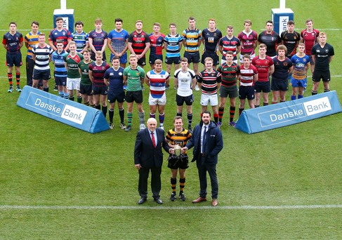 Up for the cup: Ian Russell, district manager at Danske Bank, and John McKibbin, president of IRFU (Ulster Branch), join the captains of this year's competing teams at Kingspan Stadium yesterday