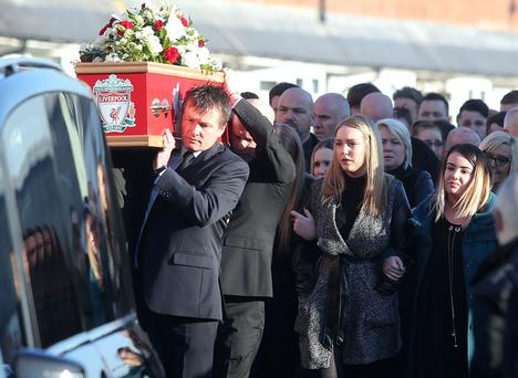 Family and friends of Jamie Burns walk behind his coffin