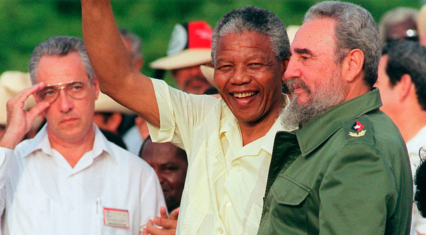 (FILES) This file photo taken on July 26, 1991 shows African National Congress (ANC) President Nelson Mandela saluting the crowd next to Cuban leader Fidel Castro in Matanzas, Cuba. AFP/Getty Images