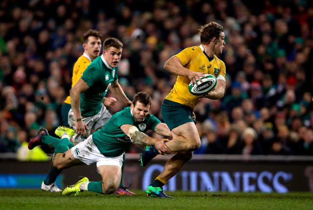 Australia's Michael Hooper is tackled by Ireland's Jared Payne during the Autumn International match at the Aviva Stadium, Dublin Pic: Niall Carson/PA Wire.