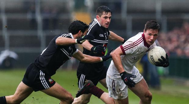 Hunted down: Kilcoo's Niall Branagan moves in to tackle Slaughtneil's Se McGuigan during yesterday's Ulster Club showdown in Armagh