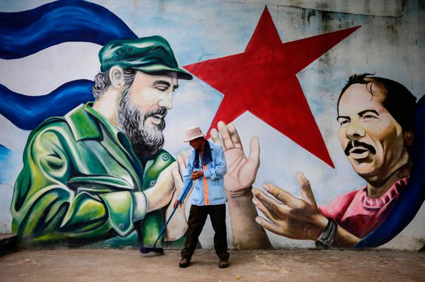 A municipal worker sweeps the floor in front of a mural depicting Cuban revolutionary leader Fidel Castro (L) and Nicaraguan President Daniel Ortega at Cuba square in Managua on November 26, 2016, the day after Castro died. AFP/Getty Images