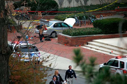 Police investigate the scene where an individual used a car to crash into a group of students outside of Watts Hall on the Ohio State University campus