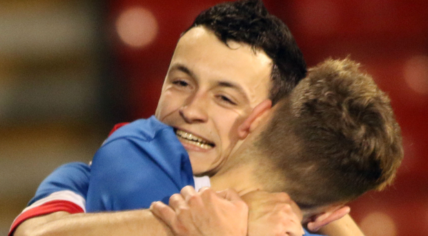Man of the moment: Linfield Swifts ace Jonny Frazer is embraced after finding the net