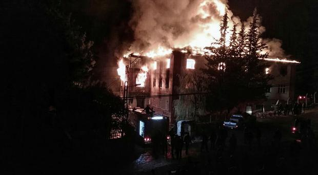 Flames rise from a fire in a school dormitory, in Aladag, Adana in southern Turkey, Tuesday, Nov. 29, 2916. (DHA via AP)