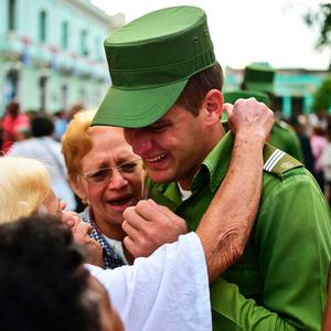 A soldier is comforted after the urn with the ashes of Cuban leader Fidel Castro was driven through Santa Clara on December 1, 2016 during its four-day journey across the island for the burial in Santiago de Cuba. A military jeep is taking the ashes of Fidel Castro on a four-day journey across Cuba, with islanders lining the roads to bid farewell to the late communist icon. Castro died at 90 on November 25, 2016 and will be buried in the eastern city of Santiago de Cuba on Sunday. / AFP PHOTO / RONALDO SCHEMIDTRONALDO SCHEMIDT/AFP/Getty Images