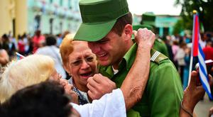 A soldier is comforted after the urn with the ashes of Cuban leader Fidel Castro was driven through Santa Clara on December 1, 2016 during its four-day journey across the island for the burial in Santiago de Cuba. AFP/Getty Images