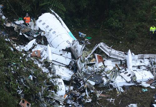 Rescue workers stand at the wreckage site of a chartered airplane that crashed outside Medellin, Colombia