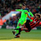 Liverpool's Roberto Firmino (left) and AFC Bournemouth's Nathan Ake (right) battle for the ball during the Premier League match at the Vitality Stadium, Bournemouth. PRESS ASSOCIATION Photo. Picture date: Sunday December 4, 2016. See PA story SOCCER Bournemouth. Photo credit should read: Adam Davy/PA Wire. RESTRICTIONS: EDITORIAL USE ONLY No use with unauthorised audio, video, data, fixture lists, club/league logos or