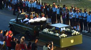 Cubans attend the passage of the urn with the ashes of Cuban leader Fidel Castro from Revolution Square in Santiago, Cuba on its way to the cemetery