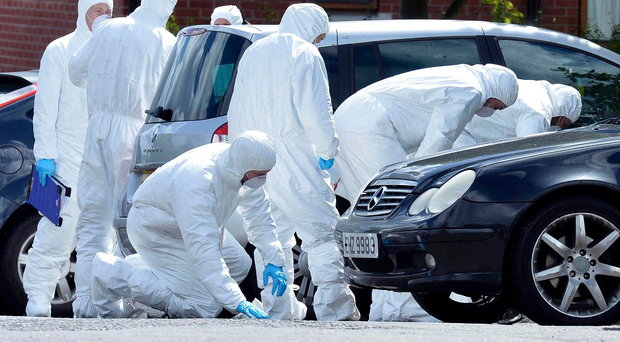 Police forensic officers at the scene in north Belfast where loyalist paramilitary boss John Boreland was shot dead