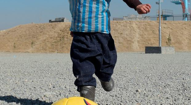 In this file photograph taken on February 1, 2016, Afghan boy five-year-old Murtaza Ahmadi, a young Lionel Messi fan, plays football in Kabul. Argentine football star Lionel Messi sent two jerseys to the five-year-old Afghan boy who became an Internet sensation when he was pictured wearing a plastic bag with