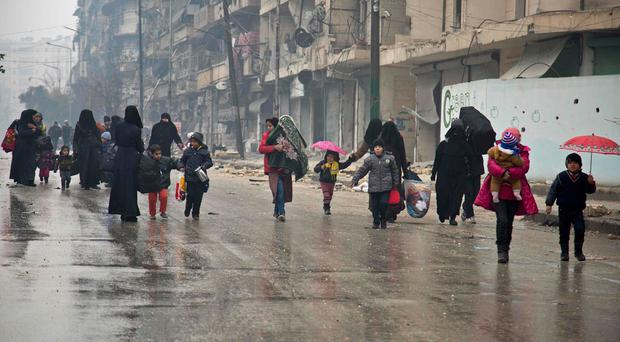 Syrians leave a rebel-held area of Aleppo towards the government-held side on December 13, 2016 during an operation by Syrian government forces to retake the embattled city. AFP/Getty Images