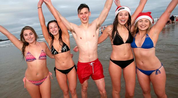 People at a charity Christmas swim at Portrush East Strand beach in Co Antrim.