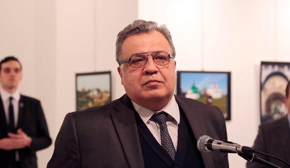 The Russian Ambassador to Turkey Andrei Karlov speaks a gallery in Ankara Monday Dec. 19, 2016. A gunman opened fire on Russia's ambassador to Turkey Karlov at a photo exhibition on Monday. The Russian foreign ministry spokeswoman said he was hospitalized with a gunshot wound. The gunman is seen at rear on the left. (AP Photo/Burhan Ozbilici)