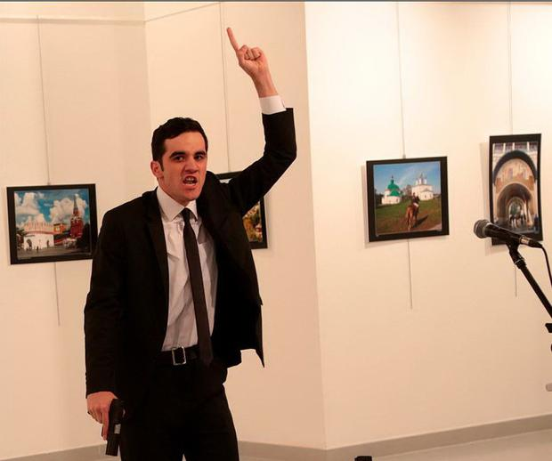 A man gestures near to Andrei Karlov, the Russian Ambassador to Turkey, on the ground, at a photo gallery in Ankara, Turkey, Monday, Dec. 19, 2016. An Associated Press photographer says a gunman has fired shots at the Russian ambassador to Turkey. The ambassador's condition wasn't immediately known. (AP Photo/Burhan Ozbilici)