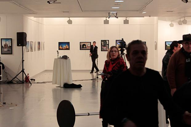 Guests leaving a gallery as a gunman (C) holds a weapon, during an attack where Andrey Karlov, the Russian ambassador to Ankara, has been shot. AFP/Getty Images