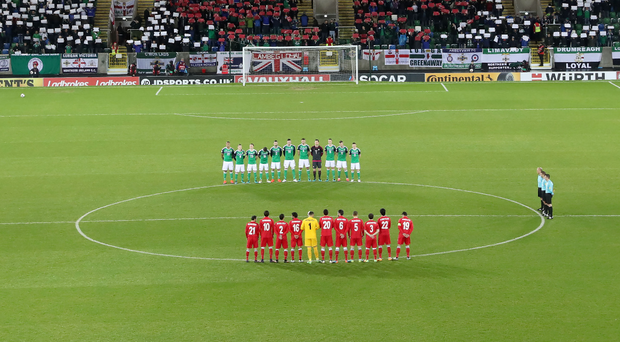 Act of Remembrance: Players and fans partake in a minute's silence, while a poppy mosaic is displayed in the Kop stand
