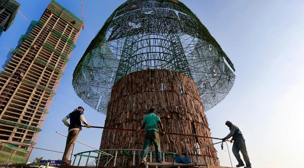 In this Thursday, Dec. 15, 2016 photo, Sri Lankan port workers carry steel rods as they try to build an enormous, artificial Christmas tree on a popular beachside promenade in Colombo, Sri Lanka. (AP Photo/Eranga Jayawardena)