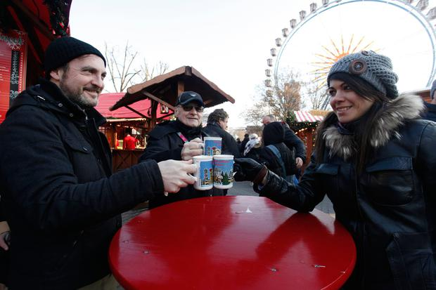 Visitors toast with mulled wine in the Christmas market at Alexanderplatz the day it reopened following an apparent terror attack on another Christmas market in the city center on December 21, 2016 in Berlin, Germany. (Photo by Michele Tantussi/Getty Images)