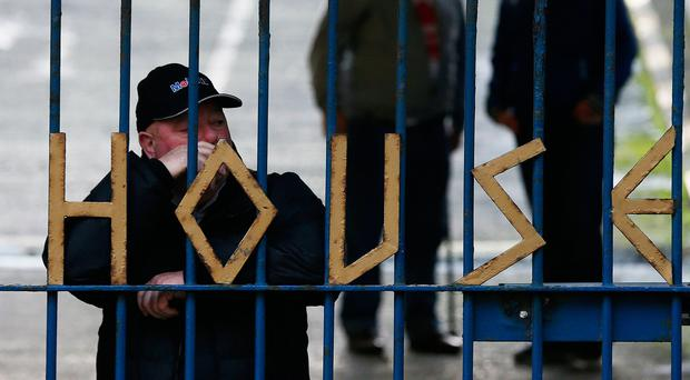File photo dated 17/12/16 of people standing behind the gates of Apollo House, as homeless campaigners who have occupied the empty office block in Dublin to shelter rough sleepers have appealed for medical supplies. PA