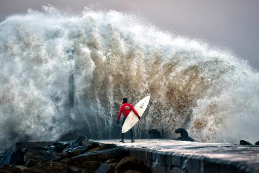 A huge wave crashes against Castlerock pier as professional surfer Al Mennie waits on a break in the swell on December 22, 2016 in Coleraine, Northern Ireland. (Photo by Charles McQuillan/Getty Images)