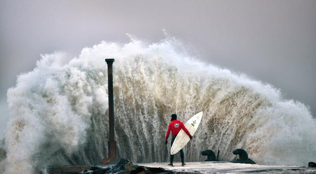 A huge wave crashes against Castlerock pier as professional surfer Al Mennie waits on a break in the swell on December 22, 2016 in Coleraine, Northern Ireland. (Picture Charles McQuillan/Getty)