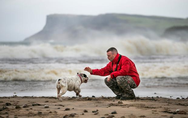 Duncan McCaughan plays with his Old English Bulldog, Daisy, on Ballycastle beach in Northern Ireland as the UK & Ireland braced for the arrival of Storm Barbara, with winds of 90mph expected to batter some parts of the country. PA