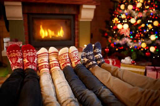 Feet in wool socks near a fireplace during Christmas time