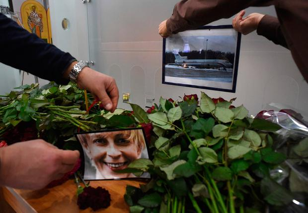 People place a portrait of the founder of Voters' League, charity activist Elizaveta Glinka, known as Dr Liza and a picture of the TU-154 airplane at the airport of the city of Sochi on December 25, 2016, after a Russian military plane which carried dozens of Red Army Choir members crashed. AFP/Getty Images