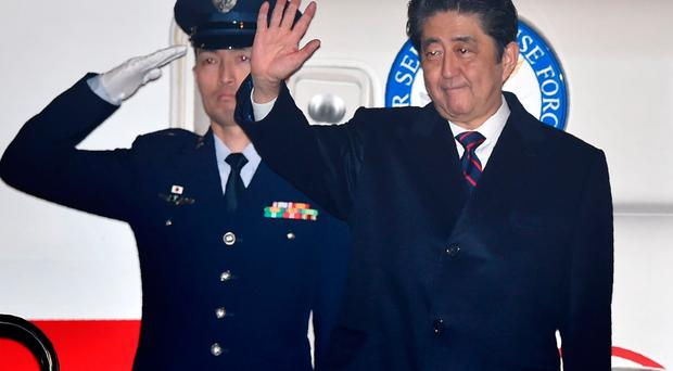 Japan's Prime Minister Shinzo Abe (R) waves before departure for Hawaii at Tokyo's Haneda airport on December 26, 2016. AFP/Getty Images