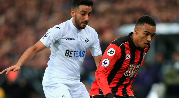 Under pressure: Neil Taylor closes in on Bournemouth's Junior Stanislas