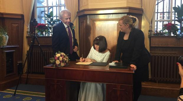 Gerry Daly and wife Rosie sign the marriage register on December 15