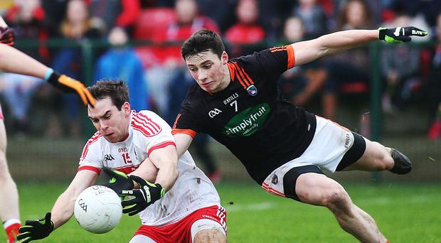 Within reach: Derry's Benny Heron battles with Armagh's Ciaran Higgins during the Dr McKenna Cup clash