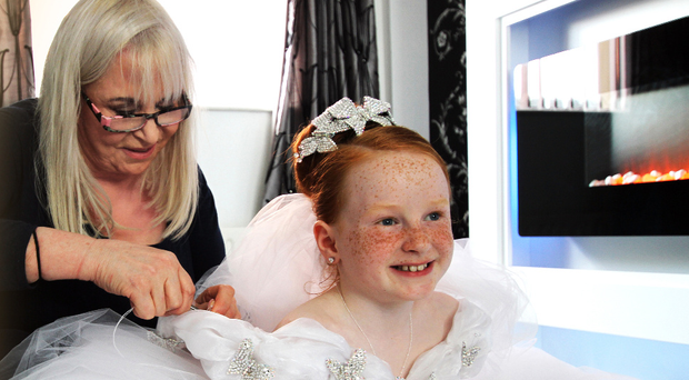 Thelma Madine with Belfast girl Cadence Courtney as she gets her Communion dress fitted