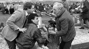 An injured man being aided by mourners, including Sinn Fein vice president Martin McGuinness (left), at Milltown Cemetery, Belfast, after a gun and bomb attack killed three and left four seriously injured, at the funerals of three IRA members killed in Gibraltar. David Jones/PA Wire