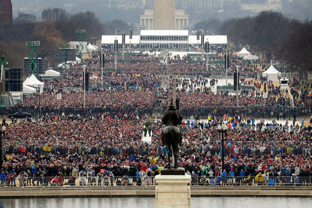 People stand on the National Mall to listen to the 58th Presidential Inauguration for President Donald Trump at the U.S. Capitol in Washington, Friday, Jan. 20, 2017. (AP Photo/Patrick Semansky)
